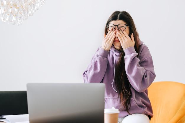 젊은 여성이 노트북 앞에서 안경을 사용한 후 눈을 문지릅니다. 눈의 통증이나 피로 개념.