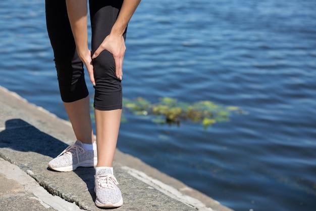 若い女性ランナーは、川の近くでトレーニング中に膝の怪我をしています。テキスト用のスペース