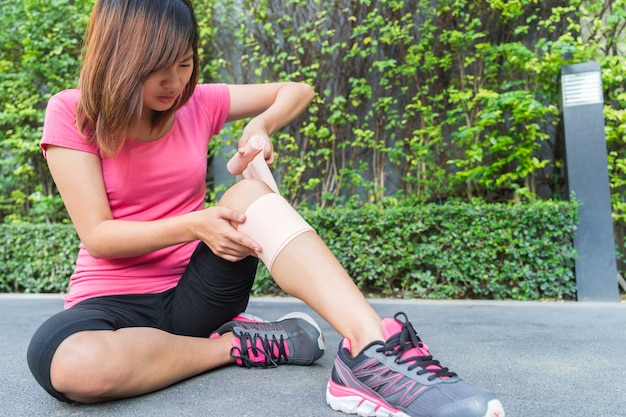 Young woman runner knee being applied bandage by herself in park. injury joint.