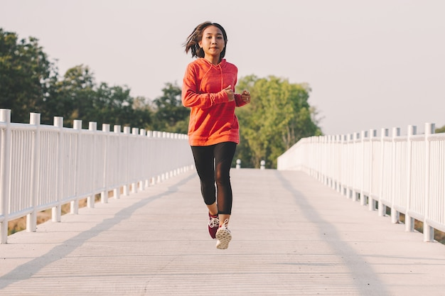 Young woman runner running on running road in city park