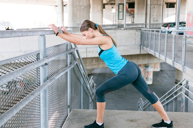 Young woman runner stretching legs before running