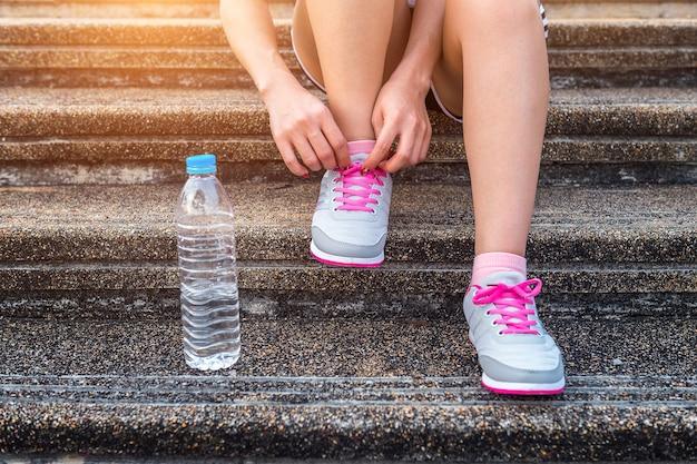 Corridore della giovane donna che lega i lacci delle scarpe. concetto di esercizio.