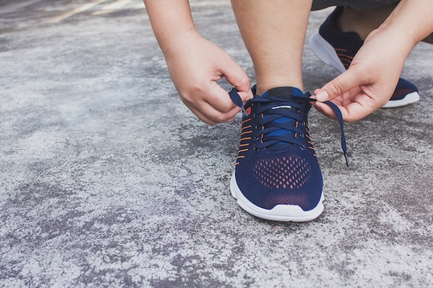 Young woman runner tying shoelaces
