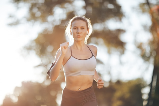 Young woman running during sunny morning