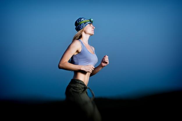 暗闇の中で走っている若い女性