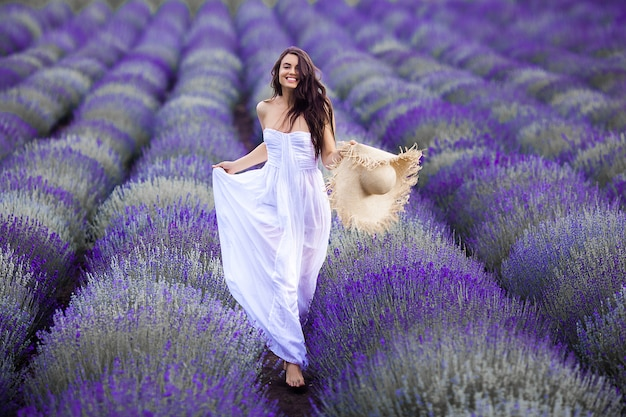 Young woman running in the lavender field. beautiful woman on summer floral background