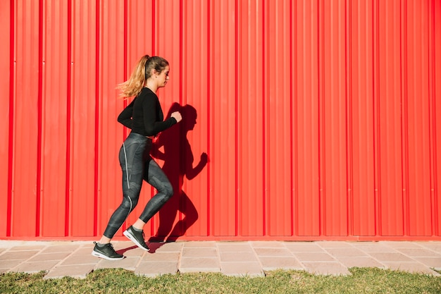 Young woman running near red wall