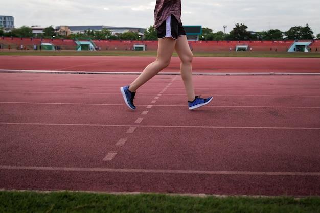 경기장 트랙에서 실행되는 젊은 여자.