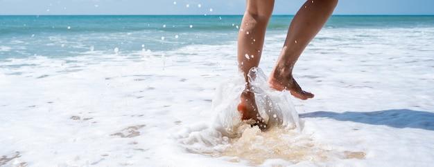 晴れた日に熱帯のビーチで走っている若い女性、夏休みのコンセプト