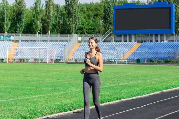 Young woman running on racetrack stadium.