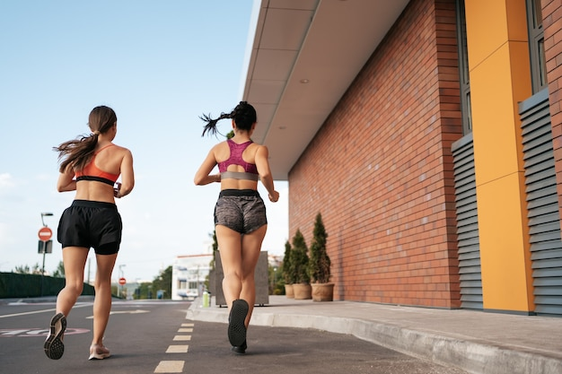 Young woman running on sidewalk in morning. health conscious concept. active girls jogging together on road in the city.