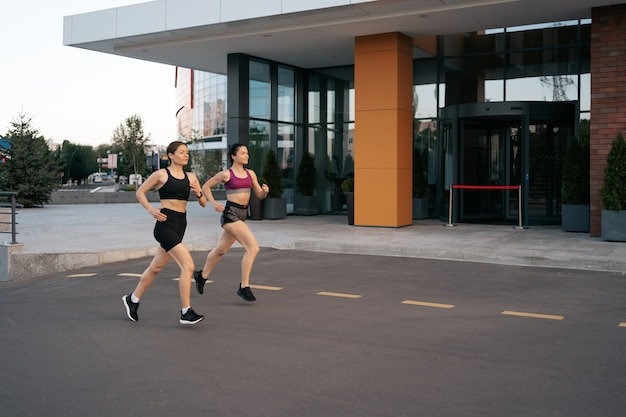 Young woman running on sidewalk in morning. health conscious concept. healthy active lifestyle.