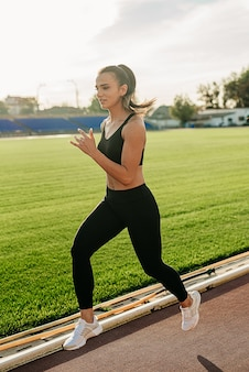 Young woman running on a sunny morning on the stadium track