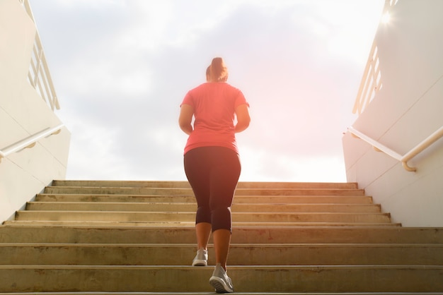 Young woman running up on stone stairs with sun spot background. workout and diet concept.