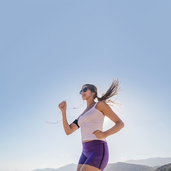 Young woman running with blue sky at the background