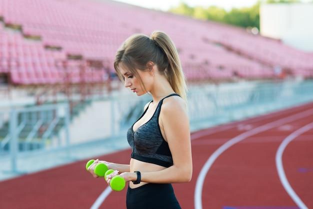 スタジアムでダンベルを手に持って走っている若い女性。スポーツと健康的なコンセプト。