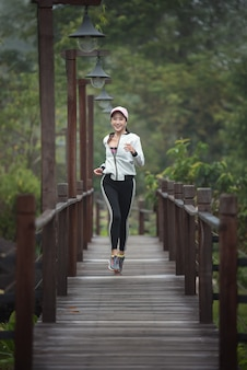 Young woman running on wood bridge