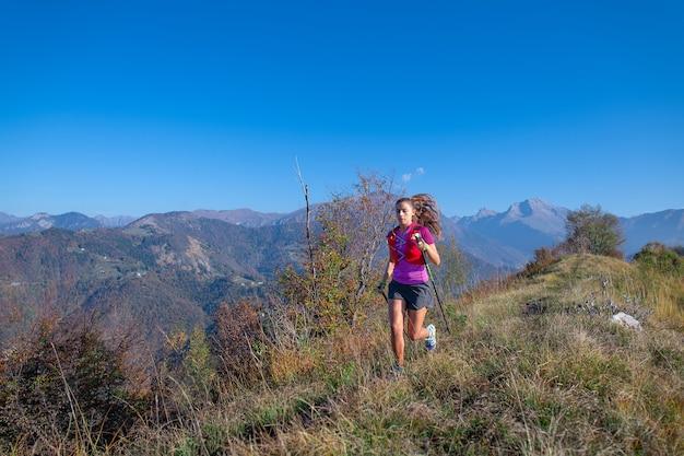 젊은 여자는 산에서 기둥으로 실행됩니다.