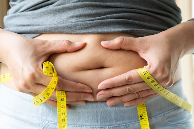 Young woman's belly with measurement tape, women diet style concept