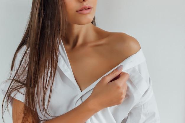Тело молодой женщины с гладкой кожей в белой рубашке