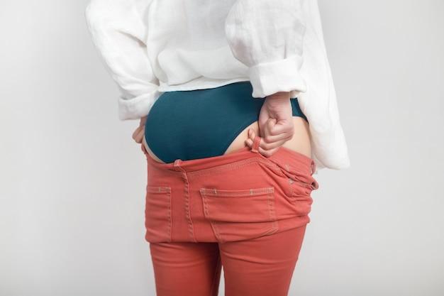 Низ молодой женщины не влезает в прошлогодние штаны. диета, избыточный вес, концепция ожирения.