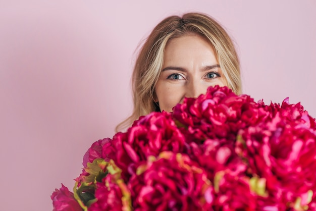 Young woman's face behind the beautiful roses bouquet against pink backdrop