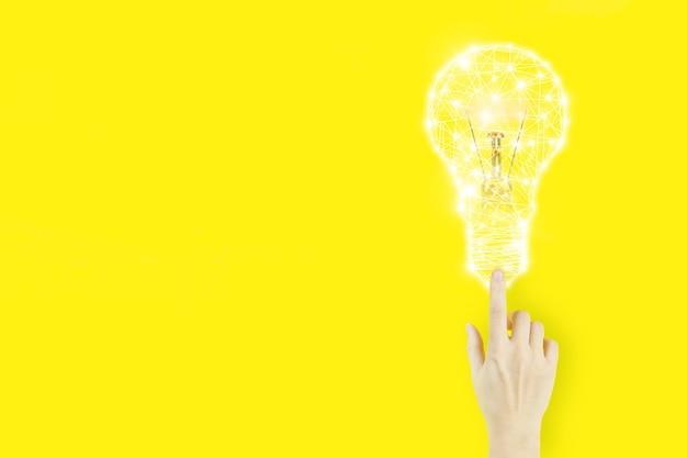노란색 배경에 전구 홀로그램으로 가리키는 젊은 여성의 손 손가락. 창의적인 아이디어. 아이디어와 혁신의 개념입니다.