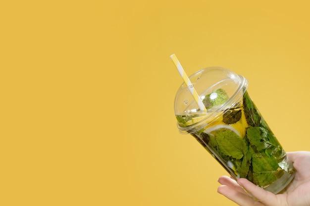 Рука молодой женщины, держащая мохито в пластиковом стаканчике с пластиковой соломкой на желтом фоне