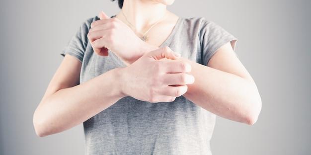Рука молодой женщины чешется