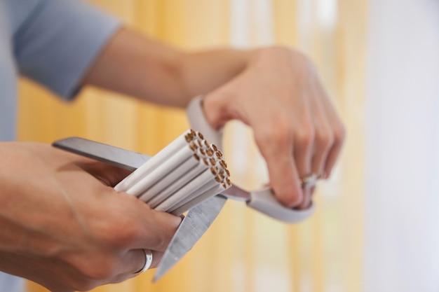 Руки молодой женщины режут сигареты ножницами. бросьте курить, боритесь с никотиновой зависимостью. крупным планом ножницы, режущие много сигарет. концепция борьбы с курением и здорового образа жизни. копировать пространство