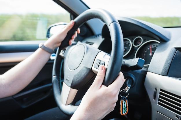 도로 여행에 차를 운전하는 젊은 여자의 손.