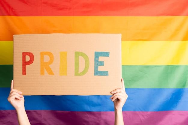 後ろに虹色の旗が付いた色付きの文字で書かれたプライドという言葉で段ボールの看板を持っている若い女性の手