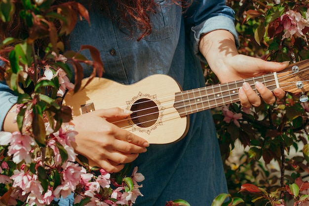 Young woman's hands holding ukulele on a  of blooming apple trees