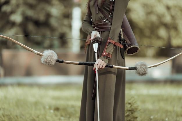 Руки молодой женщины со стрелами и луком, крупным планом