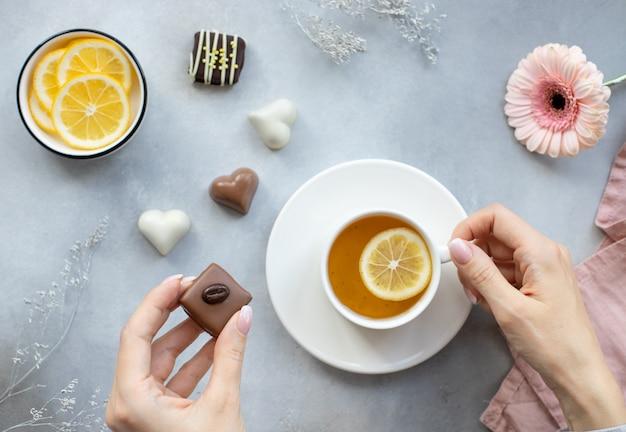 ダークチョコレート菓子と灰色の背景にお茶の白いカップを持つ若い女性の手。健康的なライフスタイルをお楽しみください。水平方向の画像、上面図、フラットレイアウト。バレンタインデーのコンセプト
