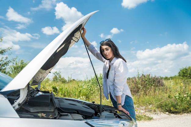 若い女性は悲しくて、損傷した車の近くで助けを待っています。