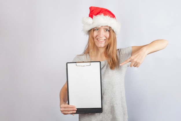 A young woman in a santa claus hat and in a simple gray t-shirt smiles and points to a blank clipboard.