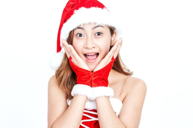 Young woman in santa claus hat surprised and open mouth on white background