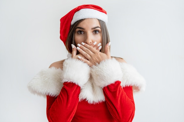 Young woman in santa claus outfit covering mouth in surprise