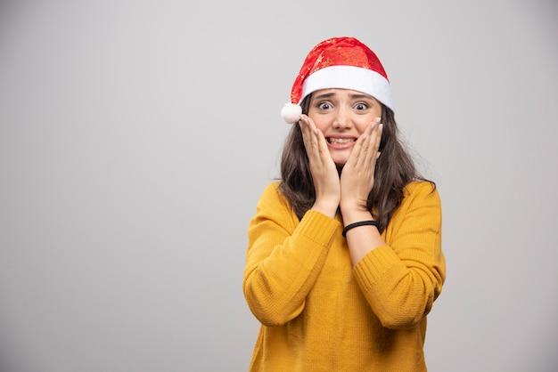 Giovane donna in cappello rosso di babbo natale in posa su un muro bianco.