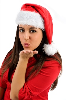 Young woman in a santa hat blowing a kiss