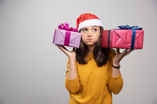 Young woman in santa hat carrying christmas presents .