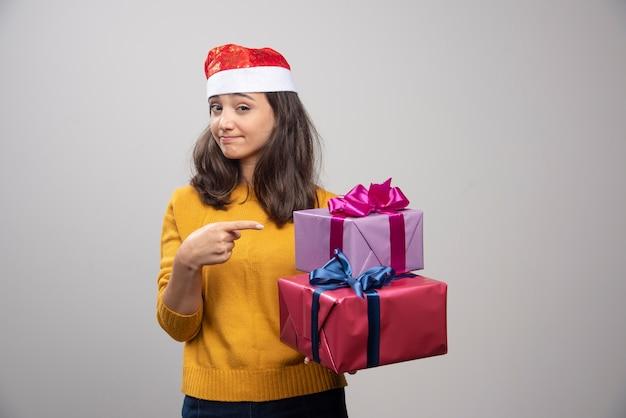 Giovane donna in cappello della santa che trasportano i regali di natale.
