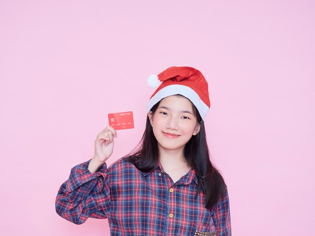 Young woman in santa hat holding credit card on pink wall.