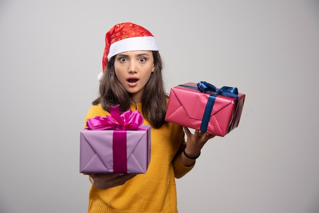 Giovane donna in cappello della santa che tiene in mano i regali di natale.