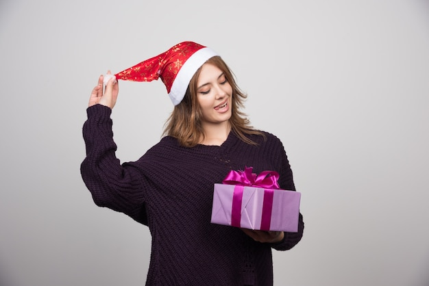 Young woman in santa hat looking at a gift box present.