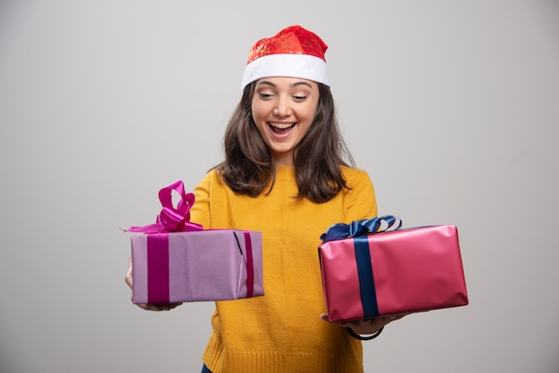 Young woman in santa hat looking at her boxes.