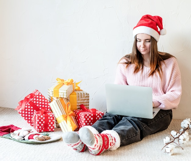 Young woman in santa hat shopping online surrounded by presents