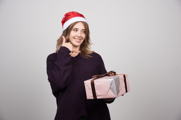 Young woman in santa's hat with a present doing phone gesture with hand and fingers .