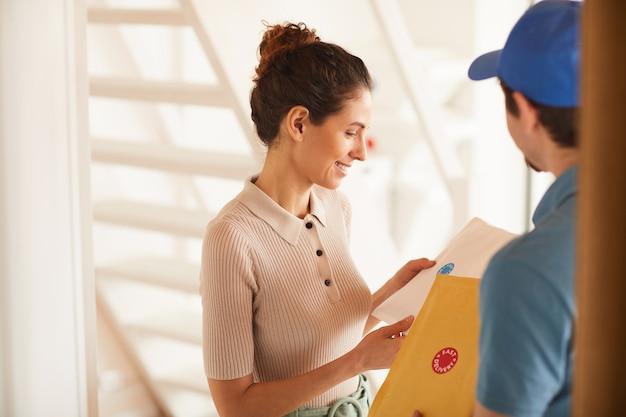 Молодая женщина довольна доставкой, получая посылки от почтальона